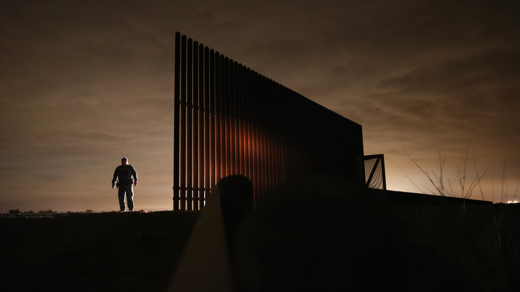 "A Border Patrol agent stands near a new fence segment while on patrol in Texas in 2012. This new design prevents people from walking through and climbing over the fence. In areas where following the Rio Grande's curves would be too expensive, new segments are built farther inland. This cuts off American land from the rest of the country. Dinan, Stephen. ""Border Fence Is in the Eye of the Beholder."" The Washington Times, 24 June 2013, http://www.washingtontimes.com/news/2013/jun/24/border-fence-eye-beholder/?page=all"