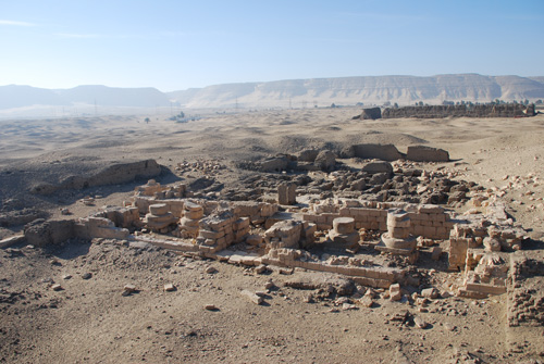 A view west from the settlement site of Abydos. In the foreground can be seen the remains of a limestone temple built by Ramesses the Great (c. 1279-1213 BC). In the mid-ground to the right are the mud-brick remains of a temple built by king Khasekhemwy (c. 2700 BC), while in the background rise the high cliffs of the western desert.