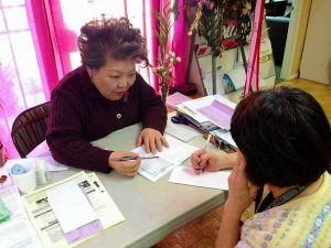 Grace Yi, a KRC volunteer, helps a client fill out a ballot.