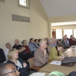 A packed audience listens attentively
