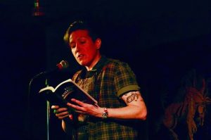 Megan Milks reading from a book at a microphone