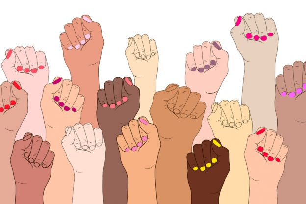 A diversity of multi-hued hands (some with painted finger nails) on a white background with fists in the air, as a symbol of resistance.
