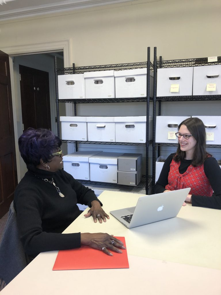 Photo of Amanda Knox capturing the oral history of Diane Straker, Administrative Assistant at the Pembroke Center, in January 2020. Both are seated at a table with shelves of file boxes behind them.
