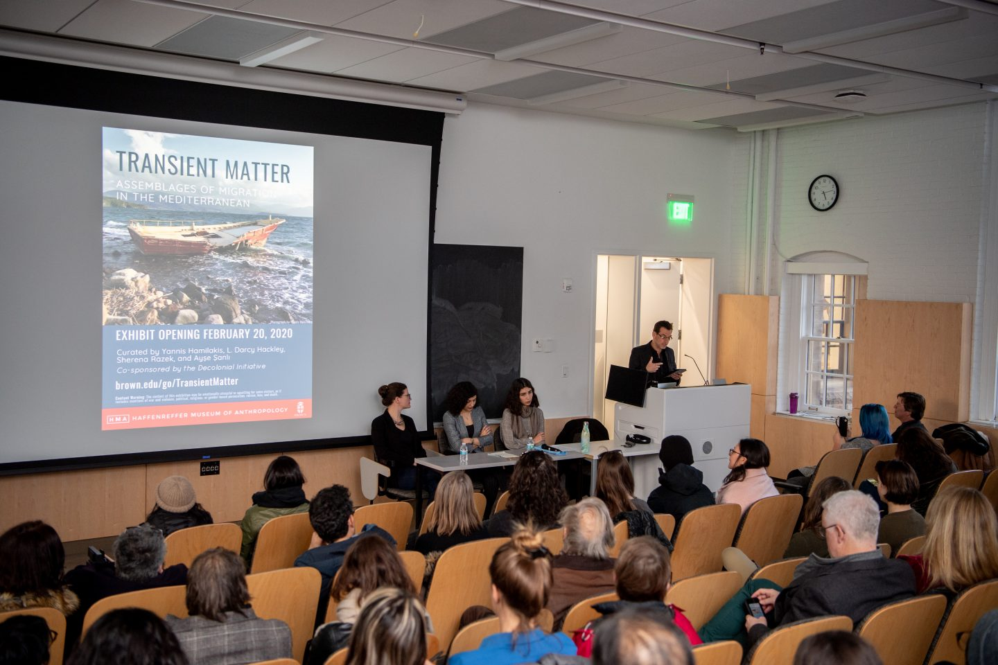 Photo of Curators Talk, including people seated in a lecture hall listening to the curators present.