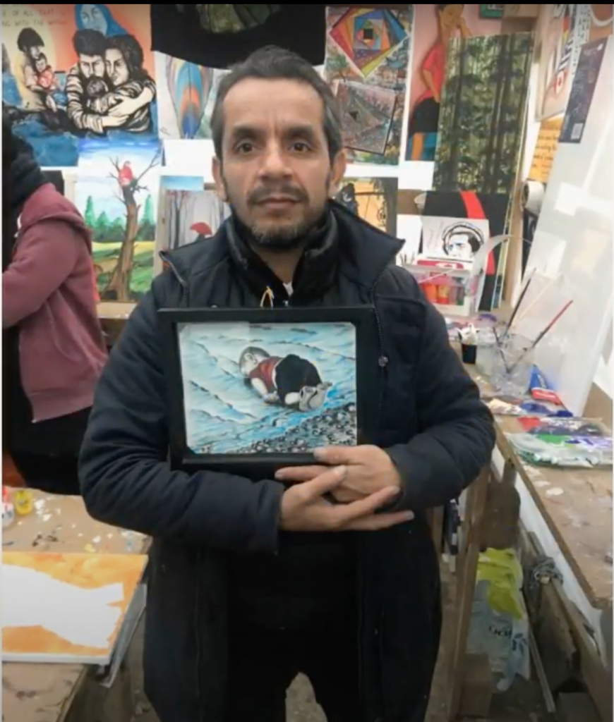 Photo of Shukran Sherzad holding his painting of a child in the water.