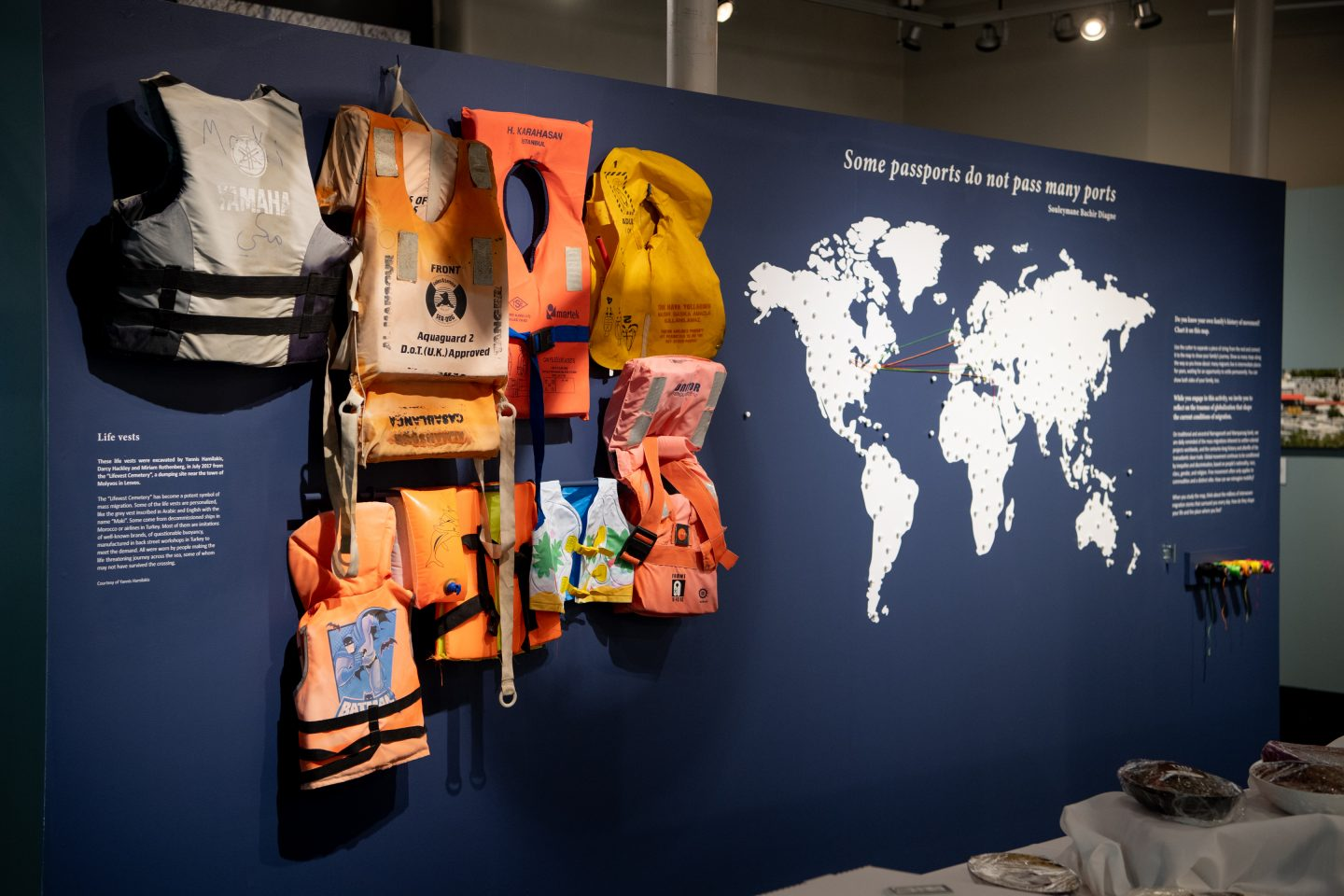 Photo from the exhibit, with discarded lifevests hung on the wall beside a world map.