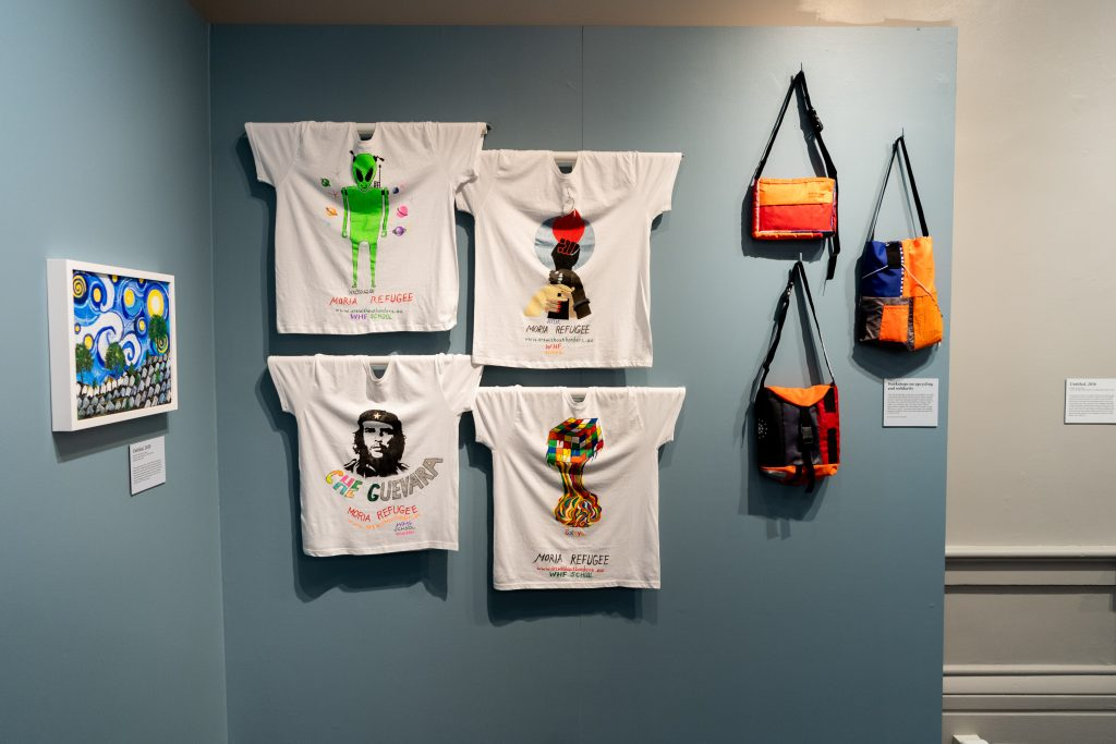 Photo of t-shirts and bags hung in the exhibit.