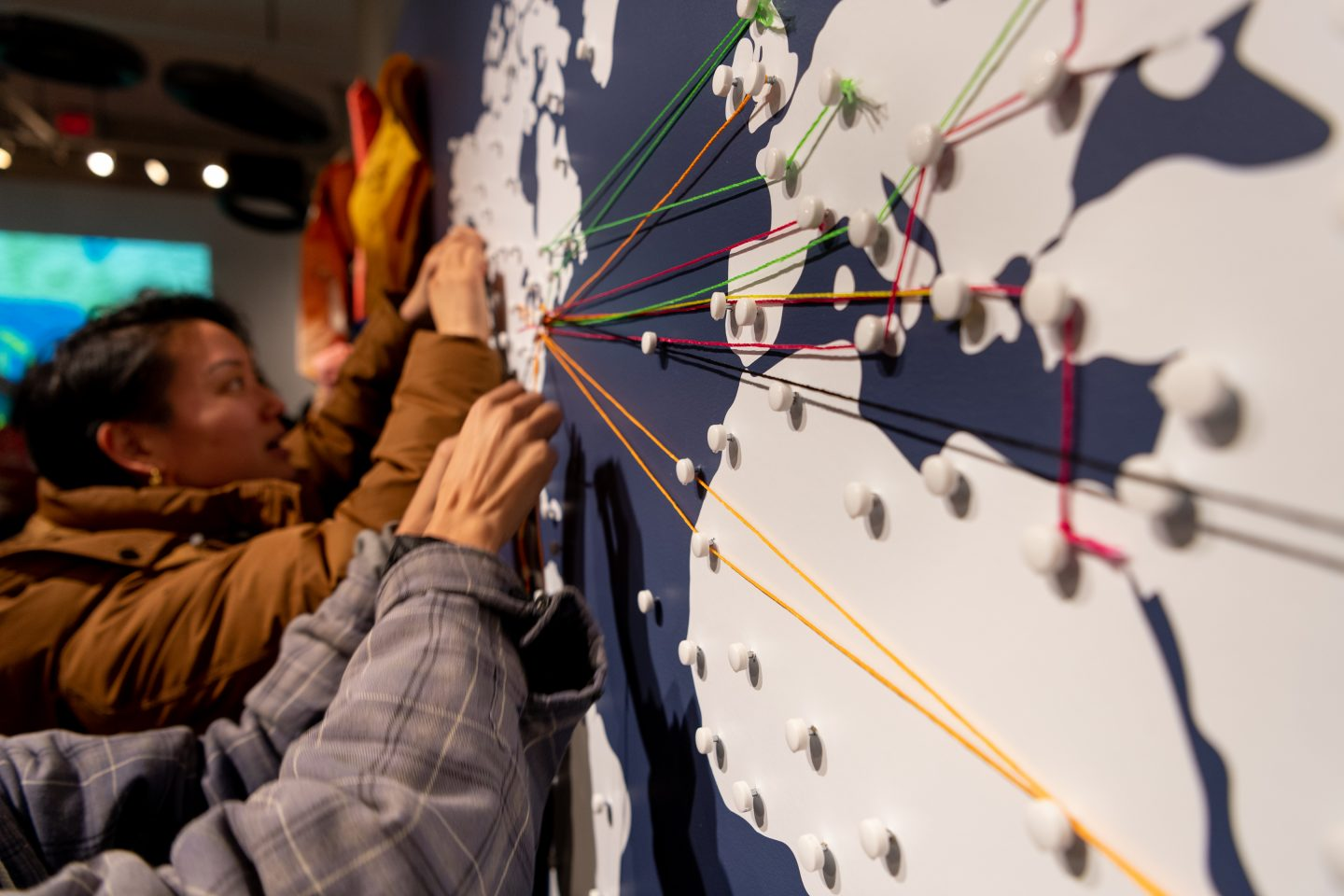 Angled photo of visitors adding string to an interactive map in the exhibit.