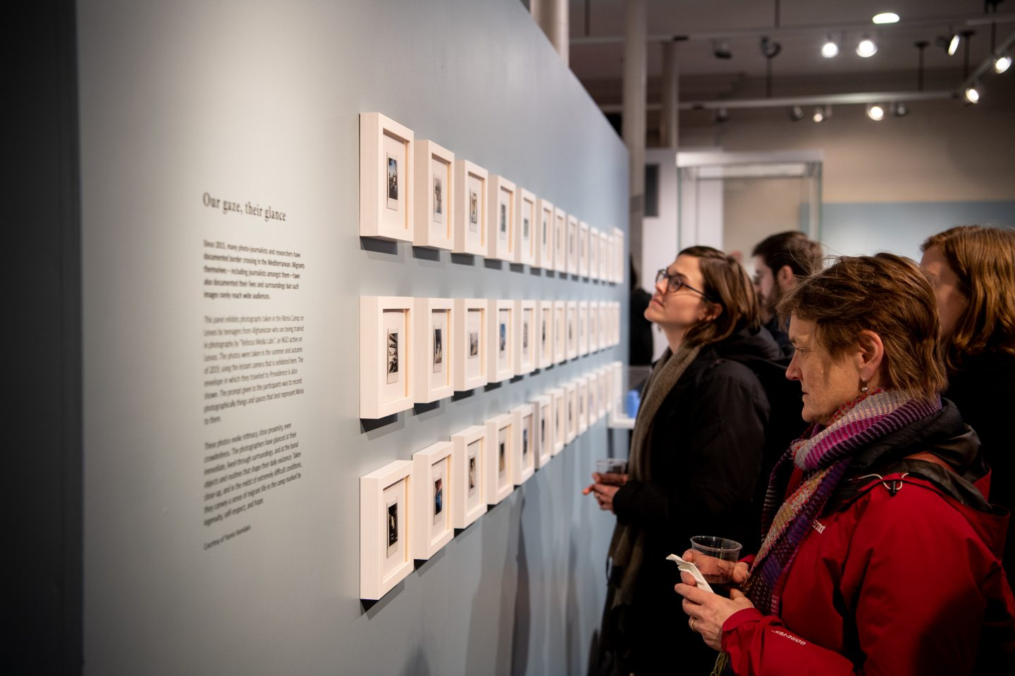 Photo of visitors to the exhibit looking at the wall of framed polaroids.