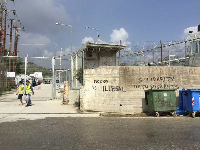 """Photo of wall and high fence, with """"No one is illegal"""" spray-painted on the wall."""