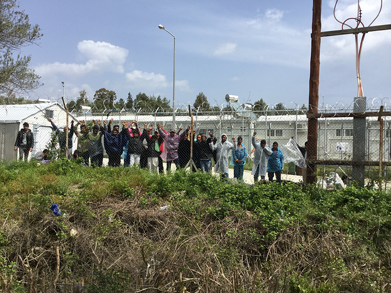 A photo of migrants protesting at the Moria registration and detention camp, seen from behind barbed wire fencing.