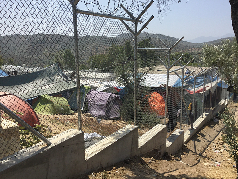 Photo of camping tents, large tents, and shipping container-style units from behind a barbed wire fence.