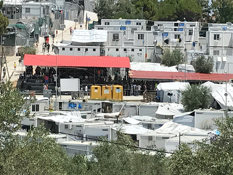 Wide photo of tents, buildings, and people congregating in the middle.