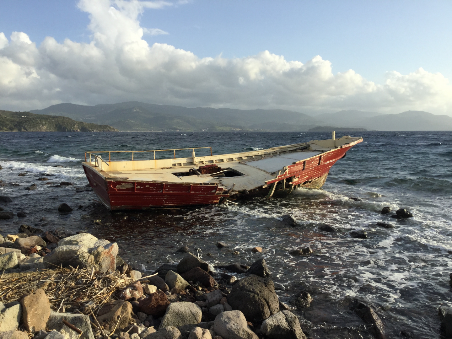 Photo of a broken wooden boat on a rocky shore.