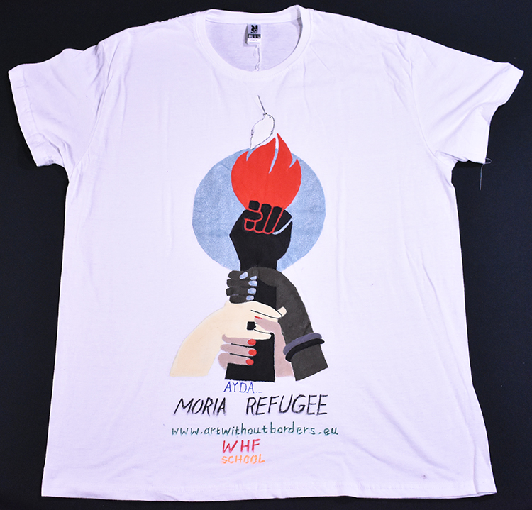 """White t-shirt painted with a torch-hand of resistance, supported by other hands of different colors, and the words """"Moria Refugee."""""""
