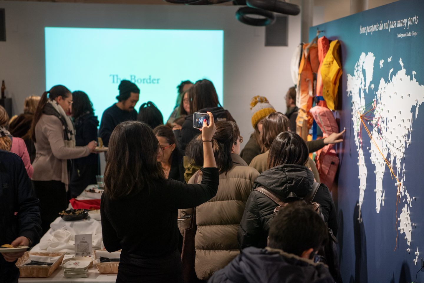 Photo of people mingling in the exhibit during the opening event.